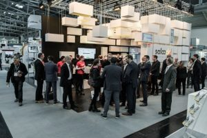 A group of people discussing next to the Saloodo! stand at the Hannover trade fair.