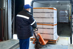 A person loading a palletized cargo into the truck.