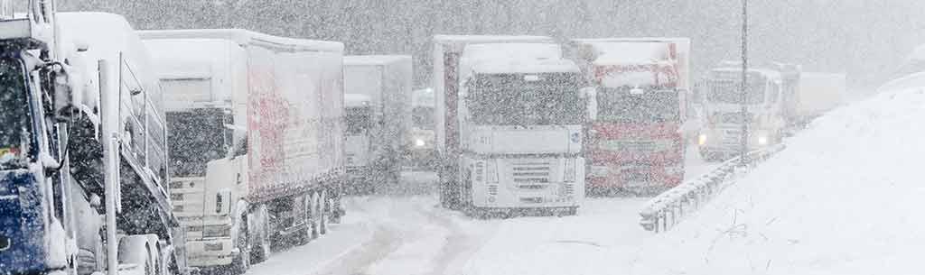 Mehrere LKW kämpfen sich bei starken Schneefall über eine Straße.