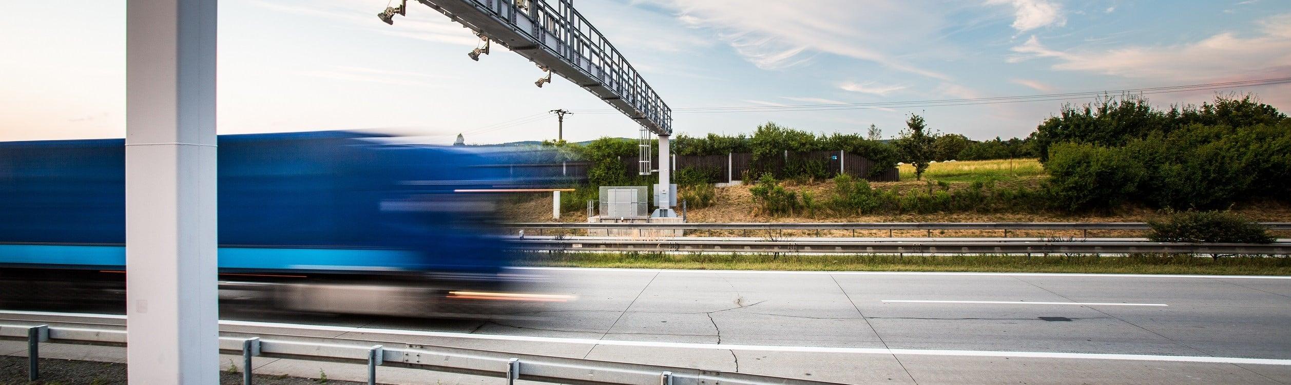 Fahrender LKW auf einer Autobahn unter einer LKW-Maut-Brücke