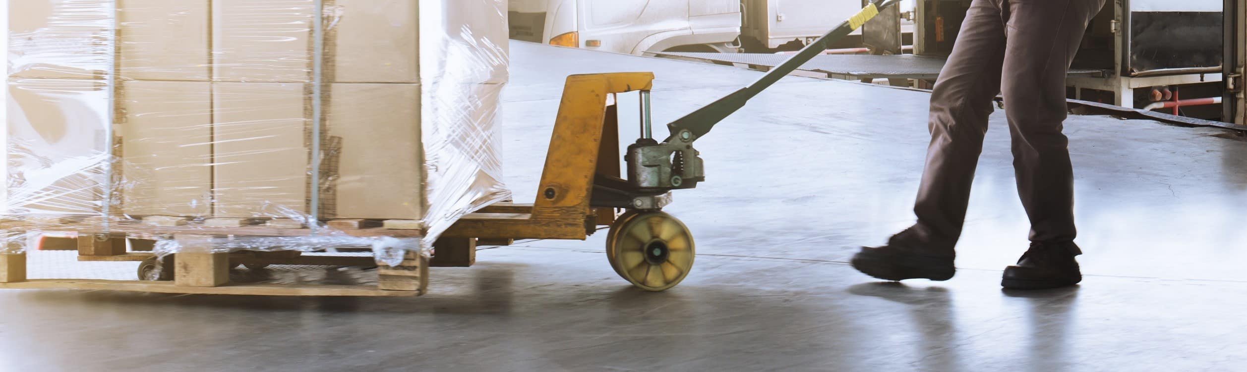 Lagerarbeiter verlädt eine Palette mit Ware für einen Palettentransport