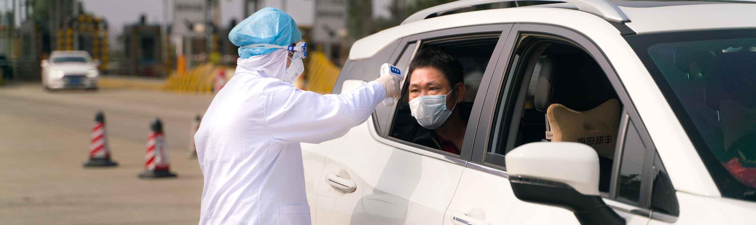 Ein Coronavirus-Kontrollposten in China auf der Autobahn. Die Ärzte kontrollieren die Temperatur eines Fahrgastes.