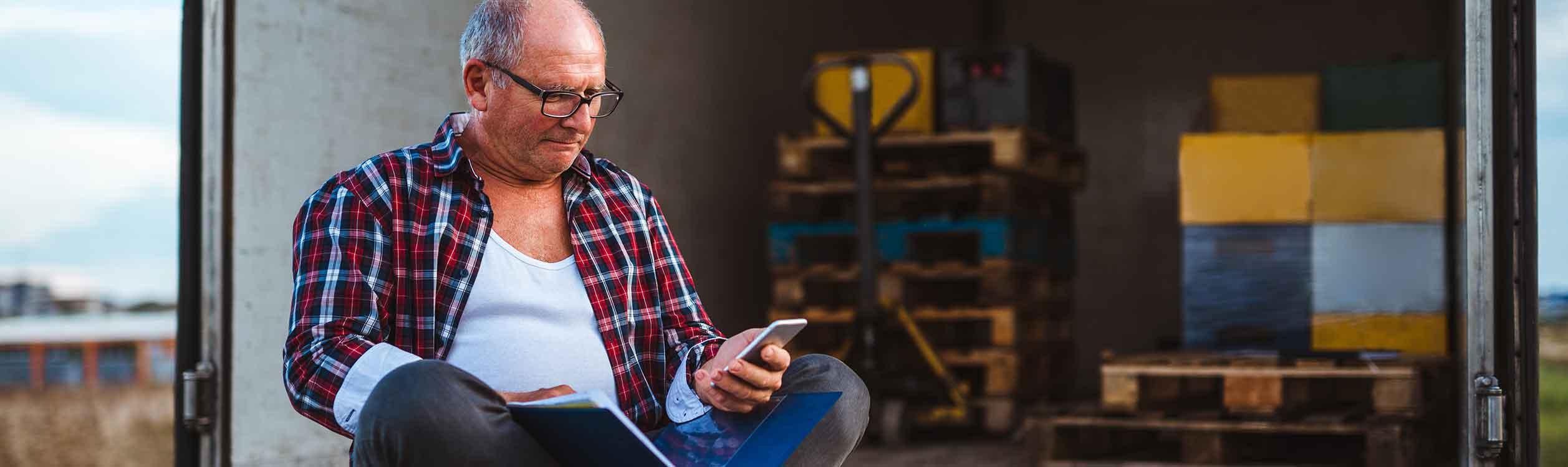 LKW-Fahrer sitzt auf der Ladefläche mit Rechnungen und schaut auf sein Handy