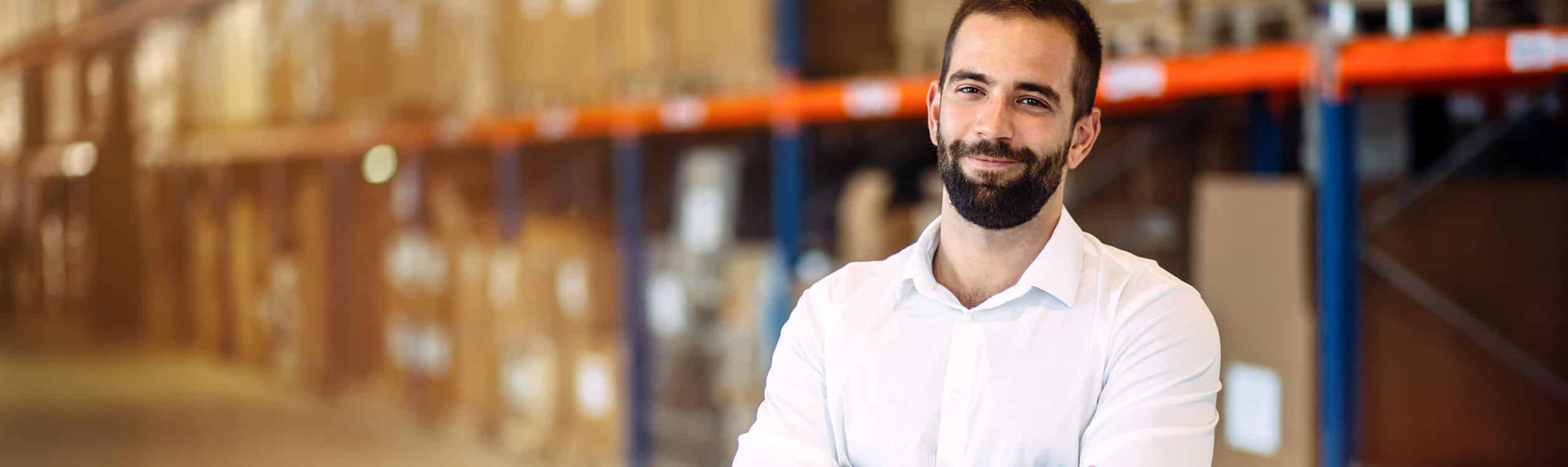 A man stands in a warehouse with his arms crossed and laughs into the camera