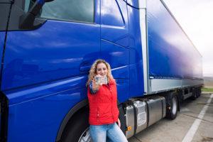 LKW-Fahrerin vor LKW zeigt ihren Führerschein