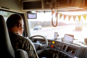 Driver in cabin of big modern truck vehicle on highway