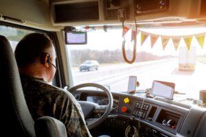Fahrer in der Kabine eines großen modernen Lkw auf der Landstraße