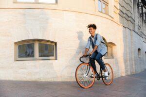 Mann fährt auf Fahrrad um eine Häuserecke