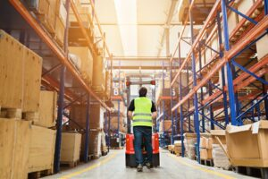 Warehouse clerk with forklift in high-bay warehouse