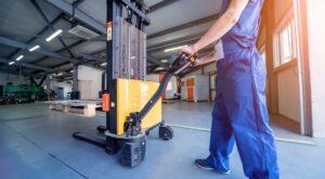 Worker with forklift in the warehouse
