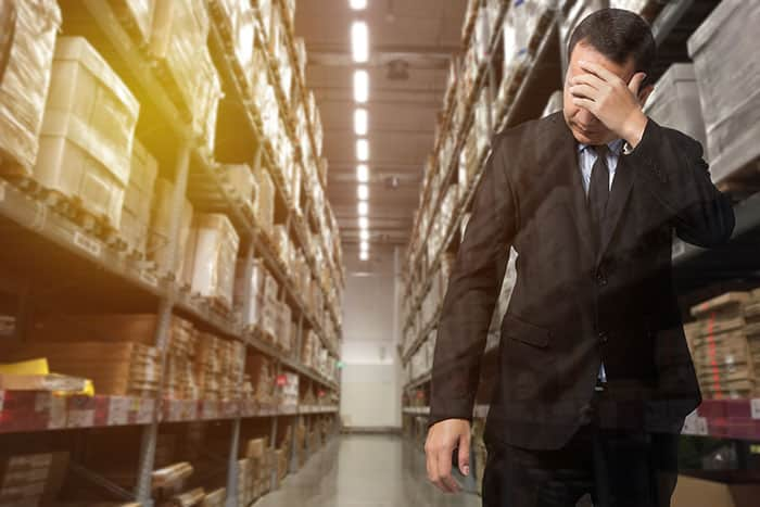 Man in business outfit standing in warehouse looking desperate